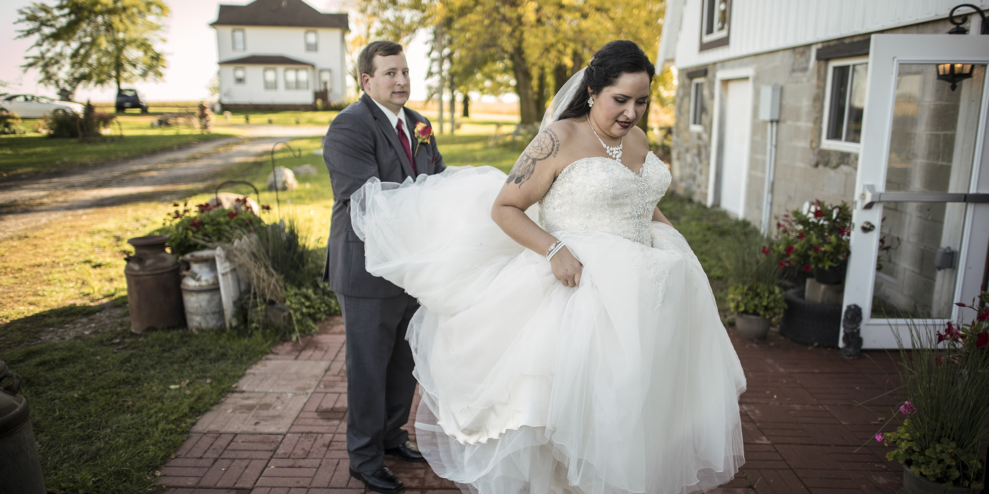 groom holding wedding dress